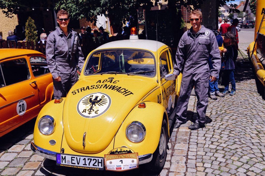 Philipp Reich und Philipp Rupprecht neben dem ADAC Südbayern Straßenwacht VW Käfer mit der Startnummer 1 bei der Pfaffenwinkel classic Rally im Juli 2017